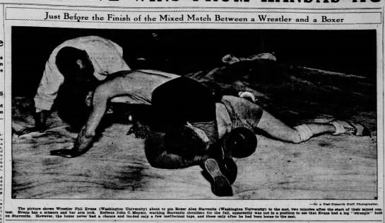 Wrestler Phil Evans controls boxer Alex Staventz on the mat under the watchful eyes of referee John C. Meyers. Both athletes were from Washington University in St. Louis