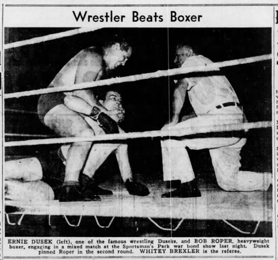 Ernie Dusek works over boxer Bob Roper at a war bond drive benefit in St. Louis-1943. Referee Whitey Brexler attentively waits for Roper to cry enough.